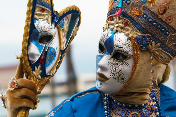 A masked reveller poses in Saint Mark Square during the Venetian Carnival in Venice